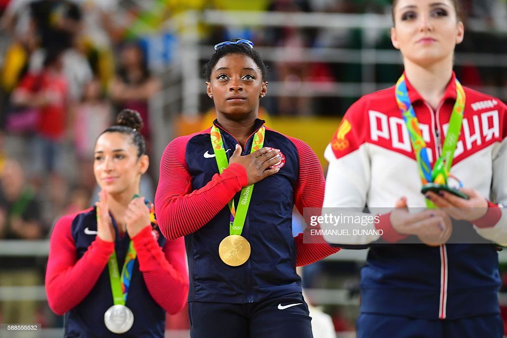 TOPSHOT - (R-L) Russia's Aliya Mustafina, US gymnast Simone Biles and US gymnast Alexandra Raisman celebrate on the podium of the women's individual all-around final of the Artistic Gymnastics at the Olympic Arena during the Rio 2016 Olympic Games in Rio de Janeiro on August 11, 2016. US gymnast Simone Biles won the event ahead of her compatiot Alexandra Raisman and Russia's Aliya Mustafina. / AFP / EMMANUEL