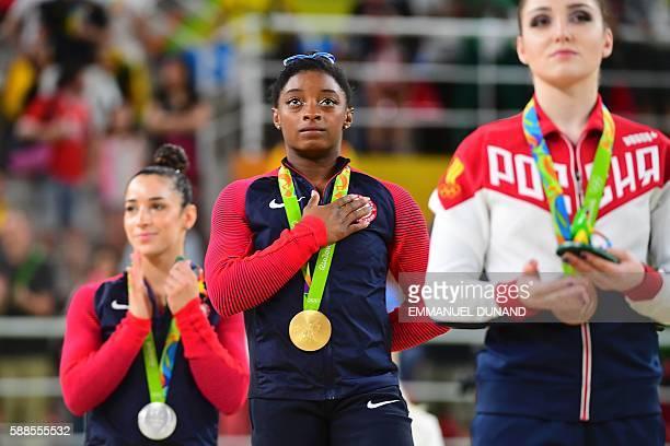 TOPSHOT Russia's Aliya Mustafina US gymnast Simone Biles and US gymnast Alexandra Raisman celebrate on the podium of the women's individual allaround...