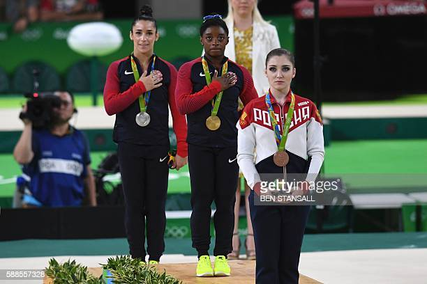 Russia's Aliya Mustafina US gymnast Simone Biles and US gymnast Alexandra Raisman celebrate on the podium of the women's individual allaround final...