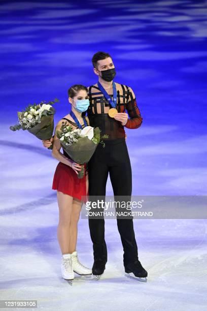 Russia's Anastasia Mishina and Aleksandr Galliamov celebrate winning gold in the pairs' free skating programme event at the ISU World Figure Skating...