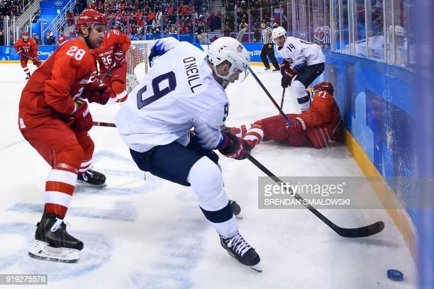 Russia's Andrei Zubarev and US Brian O'Neill vie for the puck in the men's ice hockey preliminary round group B game between the Olympic Athletes...