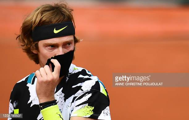 Russia's Andrey Rublev takes off his protective facemask prior to his men's singles first round tennis match against Sam Querrey of the US at the...
