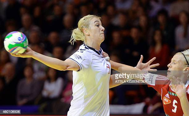 Russia's Anna Sen aims to score a goal next to Hungary's Krisztina Triscsuk during the match Hungary vs Russia at the 2014 European Women's Handball...