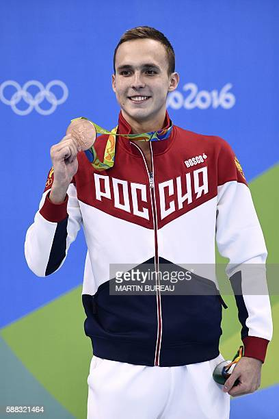 Russia's Anton Chupkov poses with his bronze medal on the podium of the Men's 200m Breaststroke Final during the swimming event at the Rio 2016...