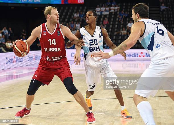 Russia's Anton Ponkrashov challenges Bosnia and Herzegovina's Alex Renfroe and Andrija Stipanovic during the 2015 EuroBasket group A basketball match...