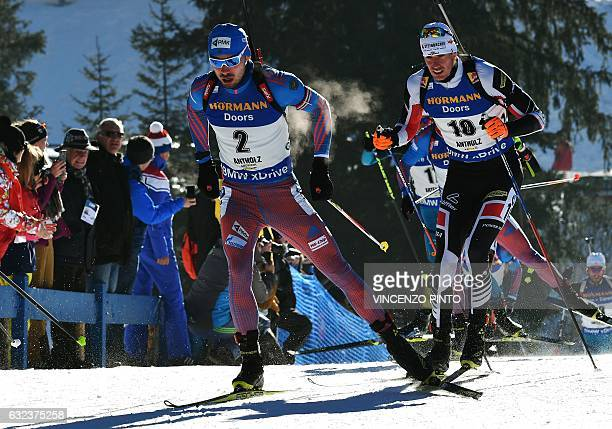 Russia's Anton Shipulin competes with Austria's Julian Eberhard during the men's 15 km mass start competition of the IBU Biathlon World Cup in...