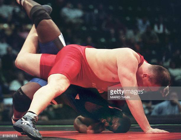 Russia's Artem Achiejev slams Cuba's Alexis Rodriguez in a 130 kg match during Russia's 2011 victory over Cuba in the World Cup of Freestyle...