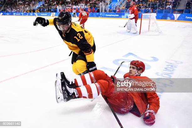 Russia's Bogdan Kiselevich lies on the ice after colliding with Germany's Brooks Macek in the men's gold medal ice hockey match between the Olympic...
