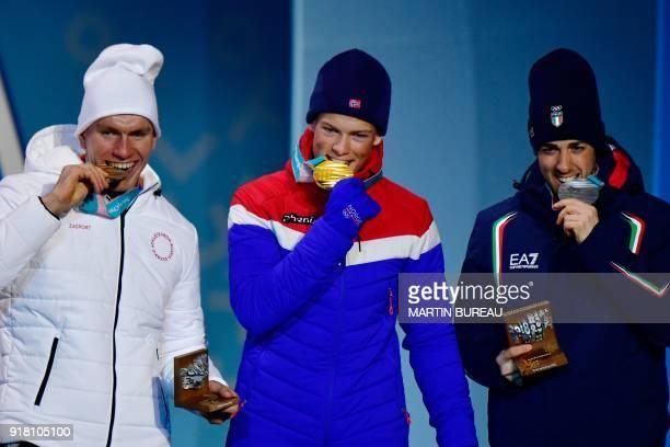 Russia's bronze medallist Alexander Bolshunov, Norway's gold medallist Johannes Hoesflot Klaebo and Italy's silver medallist Federico Pellegrino bite...