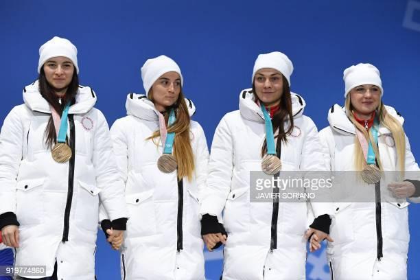 Russia's bronze medallists Natalia Nepryaeva Yulia Belorukova Anastasia Sedova and Anna Nechaevskaya pose on the podium during the medal ceremony for...