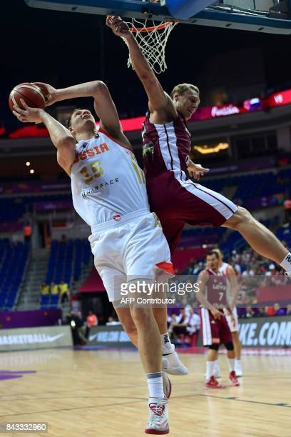 Russia's center Timofey Mozgov goes to basket next to Latvia's forward Janis Timma during FIBA Eurobasket 2017 men's group D basketball match between...