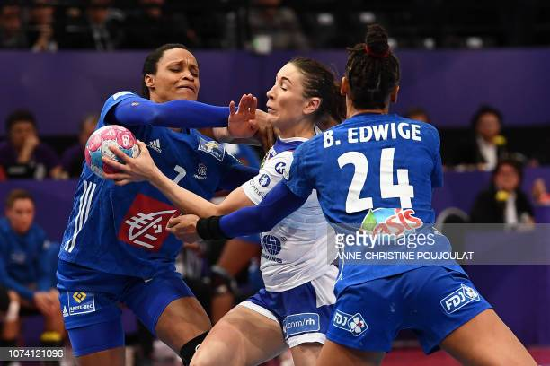 Russia's centre wing Luliia Managarova vies with France's centre back Allison Pineau and France's pivot Beatrice Edwige during the EHF EURO 2018...