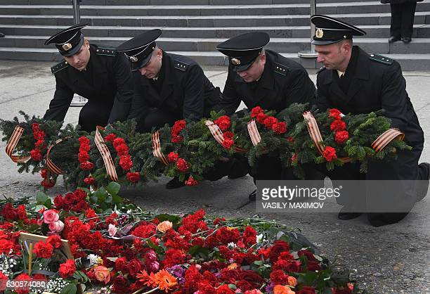 Russia's coast guard officers lay a wreath at a makeshift memorial in Sochi on December 27 two days after a military plane carrying 92 people...