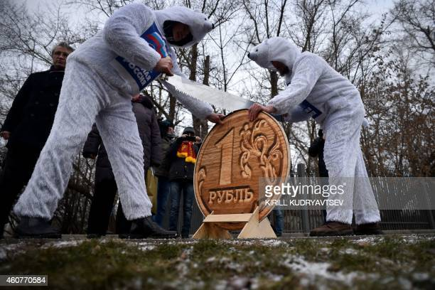 Russia's Communist Party supporters dressed as white bears symbol of proPresident party United Russia saw a model of a one Russian ruble coin during...