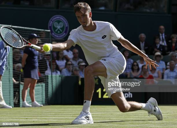 Russia's Daniil Medvedev returns to Switzerland's Stan Wawrinka during their men's singles first round match on the first day of the 2017 Wimbledon...