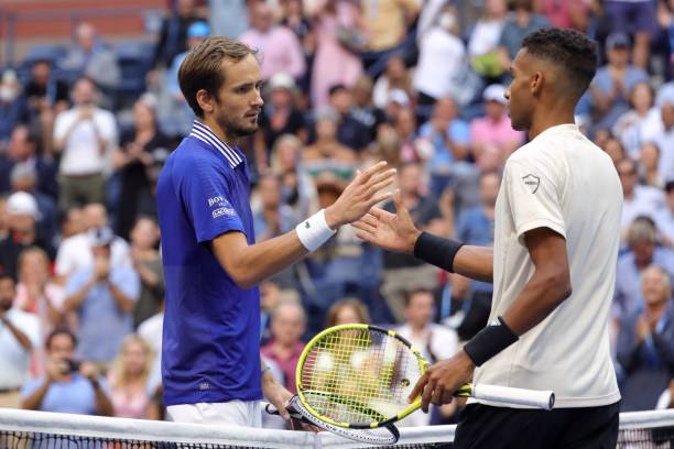 Russia's Daniil Medvedev shakes hands with Canada's Felix Auger-Aliassime at the net after winning their 2021 US Open Tennis tournament men's...