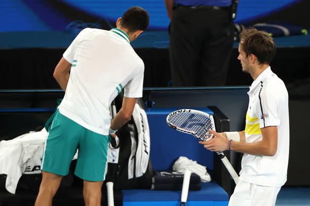 Russia's Daniil Medvedev walks past Serbia's Novak Djokovic while holding his broken racquet during their men's singles final match on day fourteen...