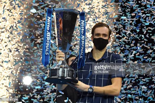 Russia's Daniil Medvedev wearing a protective face covering to combat the spread of the coronavirus, poses with the winner's trophy after his 4-6,...