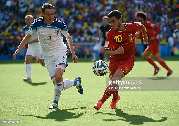 Russia's defender Aleksei and Kozlov Belgium's midfielder Eden Hazard vie for the ball during a Group H football match between Belgium and Russia at...
