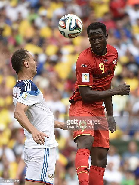 Russia's defender Aleksei Kozlov and Belgium's forward Romelu Lukaku vie for the ball during a Group H football match between Belgium and Russia at...