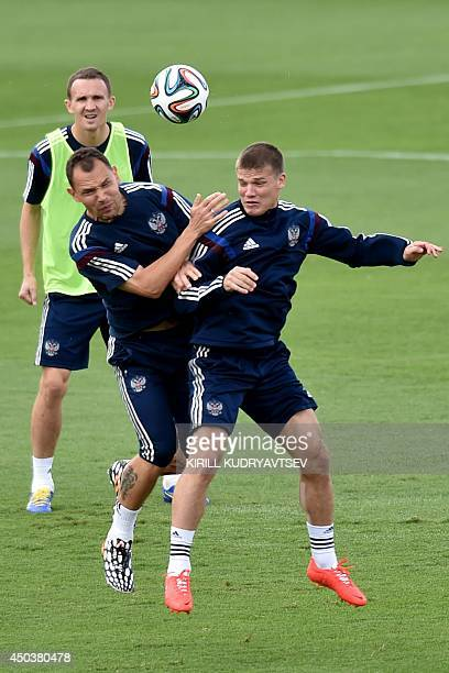 Russia's defender Aleksei Kozlov looks on as teammates defender Sergey Ignashevich and midfielder Igor Denisov compete for the ball as they take part...