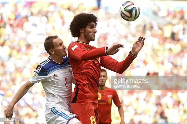 Russia's defender Aleksei Kozlov vies for the ball with Belgium's midfielder Marouane Fellaini during a Group H football match between Belgium and...