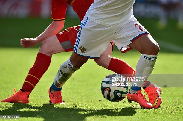 Russia's defender Alexei Kozlov and a Belgian player vie for the ball during the Group H football match between Belgium and Russia at The Maracana...