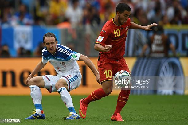Russia's defender Alexei Kozlov watches Belgium's forward Eden Hazard control the ball during the Group H football match between Belgium and Russia...