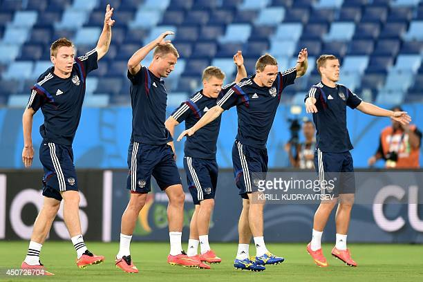 Russia's defender and captain Vasili Berezutski Russia's defender Andrey Semenov and Russia's defender Aleksei Kozlov warm up during a training...