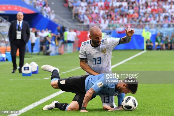 TOPSHOT Russia's defender Fyodor Kudryashov challenges Uruguay's midfielder Nahitan Nandez during the Russia 2018 World Cup Group A football match...