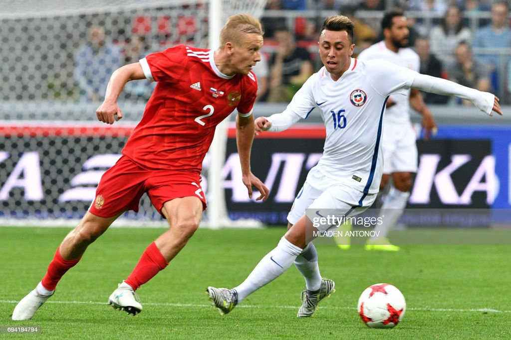 Russia's defender Igor Smolnikov (L) and Chile's forward Martin Rodriguez vie for the ball during a friendly football match between Russia and Chile at the CSKA Arena in Moscow on June 9, 2017.