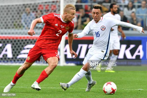 Russia's defender Igor Smolnikov and Chile's forward Martin Rodriguez vie for the ball during a friendly football match between Russia and Chile at...