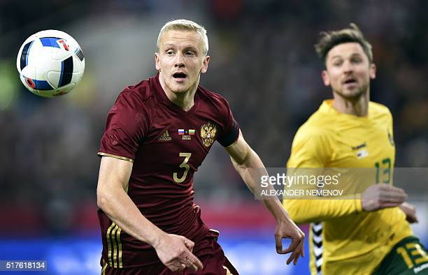 Russia's defender Igor Smolnikov and Lithuania's midfielder Saulius Mikoliunas eye the ball during their friendly football match between Russia and...