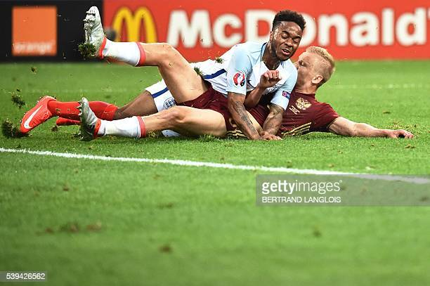 TOPSHOT Russia's defender Igor Smolnikov tackles England's midfielder Raheem Sterling during the Euro 2016 group B football match between England and...