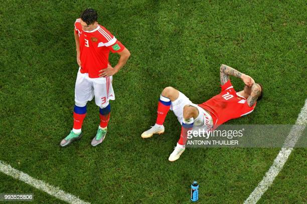 Russia's defender Ilja Kutepov and Russia's forward Fedor Smolov react at the end of the penalty shootouts of the Russia 2018 World Cup quarterfinal...