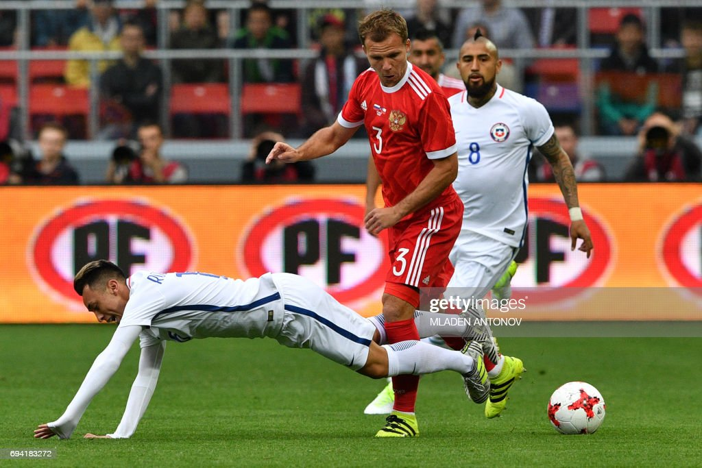 Russia's defender Roman Shishkin (C) and Chile's forward Martin Rodriguez vie for the ball during a friendly football match between Russia and Chile at the CSKA Arena in Moscow on June 9, 2017.