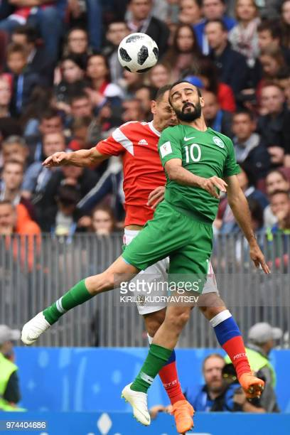Russia's defender Sergey Ignashevich vies with Saudi Arabia's forward Mohammed AlSahlawi during the Russia 2018 World Cup Group A football match...