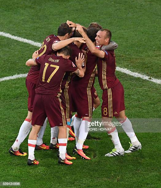 Russia's defender Vasily Berezutskiy is congratulated by teammates after scoring a goal during the Euro 2016 group B football match between England...