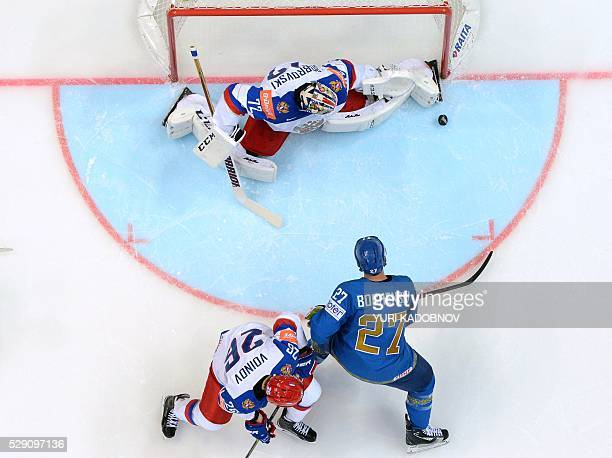Russia's defender Vyacheslav Voinov vies with Kazakhstan's forward Brandon Bochenski as Russia's goalie Sergei Bobrovski keeps a goal during the...