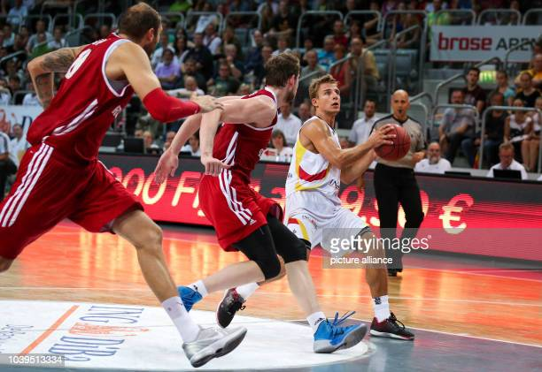 Russia's Dmitry Sokolov and Pavel Antipo try to block Germany's Heiko Schaffartzik during the Basketball DBB Supercup 2014 match between Russia and...