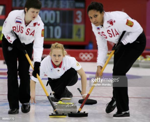 Russia's Ekaterina Galkina releases the stone flanked by team mates Olga Jarkova and Nkeirouka Ezekh during the preliminary round of the women's...