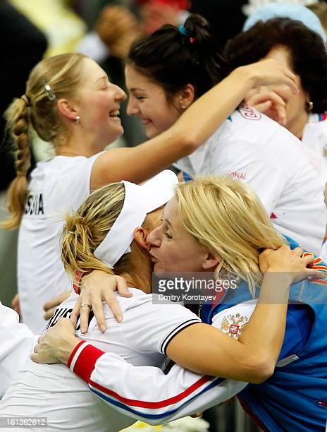 Russia's Elena Vesnina and Ekaterina Makarova celebrate with teammates after winning their doubles match against Japan's Ayumi Morita and Misaki Doi...