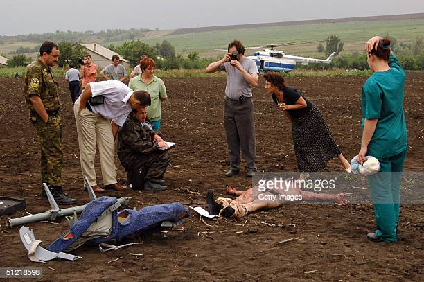 Russia's Emergencies Ministry personnel look at a body of victim of the Tupolev Tu154 passenger plane that crashed August 25 2004 near Zelenovka...