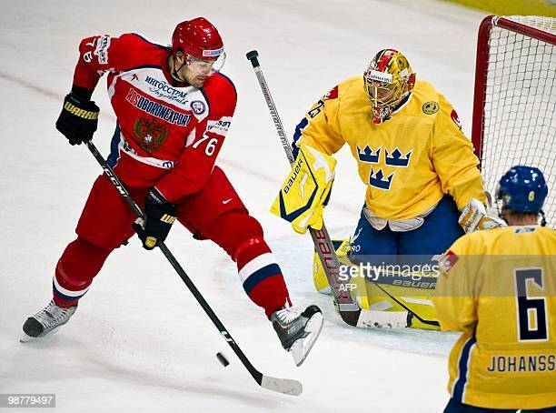 Russia's Evgeny Artyukhin, left, controls the puck in front of Sweden's goalie Jacob Markstrom during their Sweden vs. Russia match in the LG Hockey...
