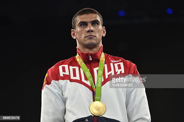 Russia's Evgeny Tishchenko poses on the podium with his medal after fighting against Kazakhstan's Vassiliy Levit during the Men's Heavy Final Bout...