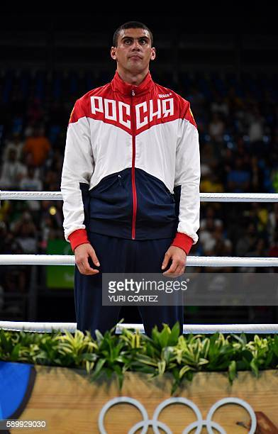 Russia's Evgeny Tishchenko stands to receive his medal after fighting against Kazakhstan's Vassiliy Levit during the Men's Heavy Final Bout match at...