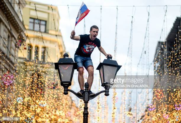Russia's fan celebrates in central Moscow after Russia won the Russia 2018 World Cup round of 16 football match against Spain on July 1 2018