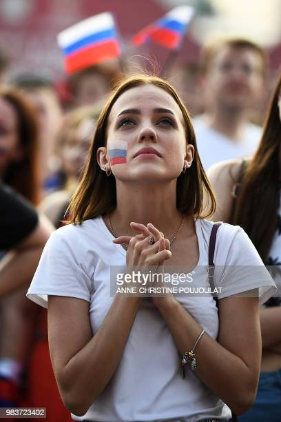 A Russia's fan reacts while watching on a giant screen in the Fans Zone of Ekaterinburg the Russia 2018 World Cup Group A football match between...