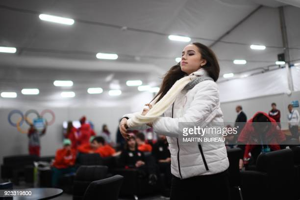 Russia's figure skating gold medallist Alina Zagitova adjusts her scarf backstage at the Athletes' Lounge during the medal ceremonies at the...