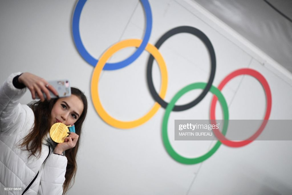TOPSHOT - Russia's figure skating gold medallist Alina Zagitova poses for a selfie in front of Olympic rings backstage at the Athletes' Lounge during the medal ceremonies at the Pyeongchang Medals Plaza during the Pyeongchang 2018 Winter Olympic Games in Pyeongchang on February 23, 2018. / AFP PHOTO / Martin BUREAU